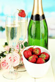 Romantic still life with champagne, strawberry and pink roses, on bright background — Stock Photo