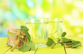Glasses of birch sap on wooden table, on green background — Stock Photo