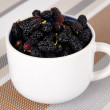Ripe mulberries in cup on table in room — Stock Photo