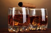 Brandy glasses with ice and cigar on wooden table on brown background — Stock Photo