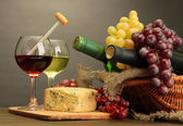 Composition with wine, blue cheese and grape on wooden table, on grey background — Stock Photo
