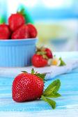 Fresas dulces en un tazón en tabla de madera azul — Foto de Stock