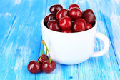 Cherry berries in cup on wooden table close-up — Stock Photo