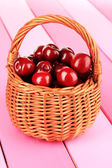 Cherry berries in wicker basket on wooden table close-up — Stock Photo