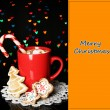 Cup of coffee with holiday candy on Christmas lights background — Stock Photo #26321395