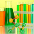 Molecule model and test tubes with colorful liquids on yellow background — 图库照片