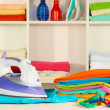 Stock Photo: Clothes and iron on table on shelves background