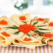 Delicious pancakes with red caviar on table in room — Stock Photo #26323343