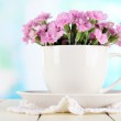 Many small pink cloves in cup on wooden table on window background — Stock Photo #26325069