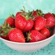 Strawberries in plate on blue background — Stock Photo #26325253