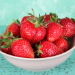 Stock Photo: Strawberries in plate on blue background