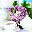 Composition with beautiful lilac flowers, tea service on wooden table on bright background — Stock Photo