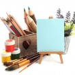 Pencils in wooden crate, paints, brushes and easel, isolated on white — Stock Photo #26328135