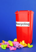 Recycling bin with papers on blue background — Stock Photo