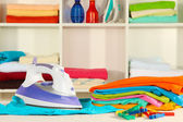 Clothes and iron on table on shelves background — Stockfoto