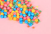 Different colorful beads on pink background — Stock Photo