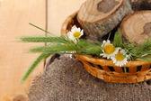 Viele Ährchen und Kamille auf Satin in Korb auf hölzernen Hintergrund — Stockfoto