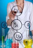 Kemist kvinna skriva formler på glas på blå bakgrund — Stockfoto