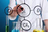 化学家女人在蓝色背景上的玻璃上写公式 — 图库照片