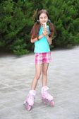Klein meisje in rolschaatsen eten smakelijke consumptie-ijs in het park — Stockfoto