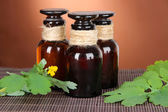 Blooming Celandine with medicine bottles on table on brown background — Stock Photo