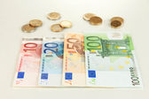 Euro banknotes and euro cents isolated on white — Стоковое фото