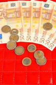 Banknoty euro i eurocentów na czerwonym tle — Zdjęcie stockowe