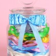 Stock Photo: Glass jar containing various colored ribbons on pink background
