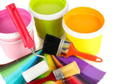 Paint pots, paintbrushes and coloured swatches close up — Stock Photo