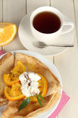 Pancakes with orange on wooden table — Stock Photo