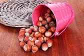 Overturned bucket with hazelnuts on wooden background — Stock Photo