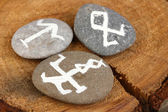 Fortune telling with symbols on stones on wooden background — Stock Photo