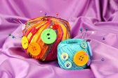Botones de colores y bolas de lana multicolor, sobre fondo de tela color — Foto de Stock
