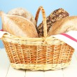 Composition with bread and rolls on wooden table, on color background — Stock Photo #26381227