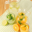 Orange and lemon lemonade in pitchers and glasses on wooden table close-up — Stock Photo