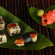 Tasty Maki sushi - Roll on green leaf on bamboo mat — Стоковая фотография
