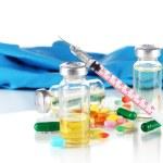 Medical bottles gloves and syringe on gray background — Stock Photo #26383861
