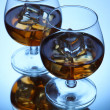 Stock Photo: Brandy glasses with ice on blue background