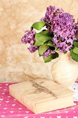Composition with lilacs on beige background — Stock Photo