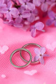Beautiful wedding rings on pink background — Stok fotoğraf
