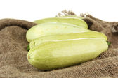 Fresh marrows on sackcloth, isolated on white — Stock Photo
