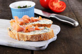 Fish sandwiches on cutting board on wooden table — Stock Photo