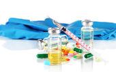 Medical bottles gloves and syringe on gray background — Stock Photo