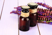 Medicine bottles and salvia flowers on purple wooden background — Stock Photo