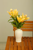 Beautiful orange lilies in vase on wooden table — Stock Photo