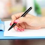 Female hand writing, on bright background — Stock Photo