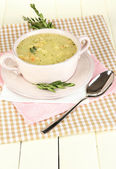 Nourishing soup in pink pan on wooden table close-up — Foto de Stock