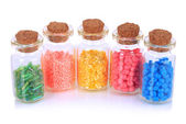 Different colorful beads in bottles isolated on white — Stock Photo