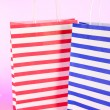 Stripped bags on light pink background — Stock Photo