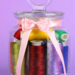 Stock Photo: Glass jar containing various colored thread on lilac background